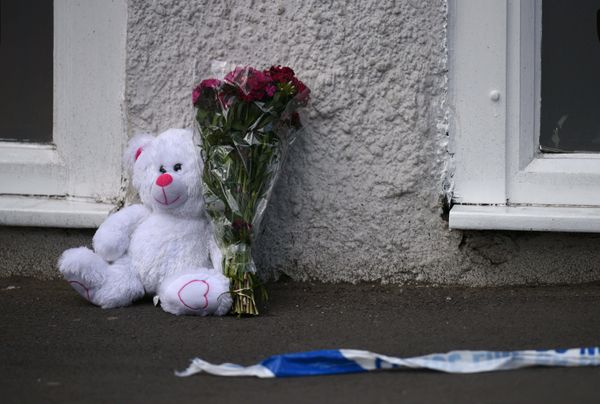 A floral tribute and a teddy bear are pictured alongside police tape near to the Manchester Arena.