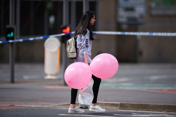 A girl wearing a t-shirt of US singer Ariana Grande carrying balloons from the Ariana Grande concert at the Manchester Arena.