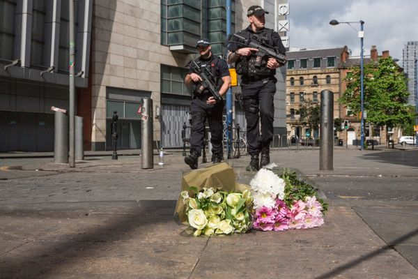Armed police patrol on Shudehill walking past the first floral tributes to the victims of the terrorist attack in Manch