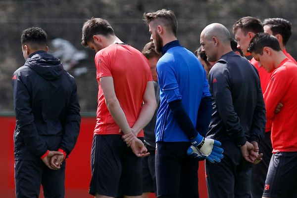 Manchester United soccer players and staff stand for a minute of silence during training honoring the people killed and wound
