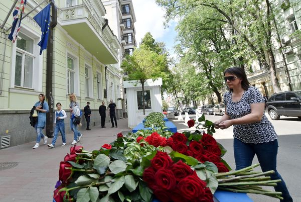 A woman lays flowers in front of the British Embassy in Kiev, Ukraine.