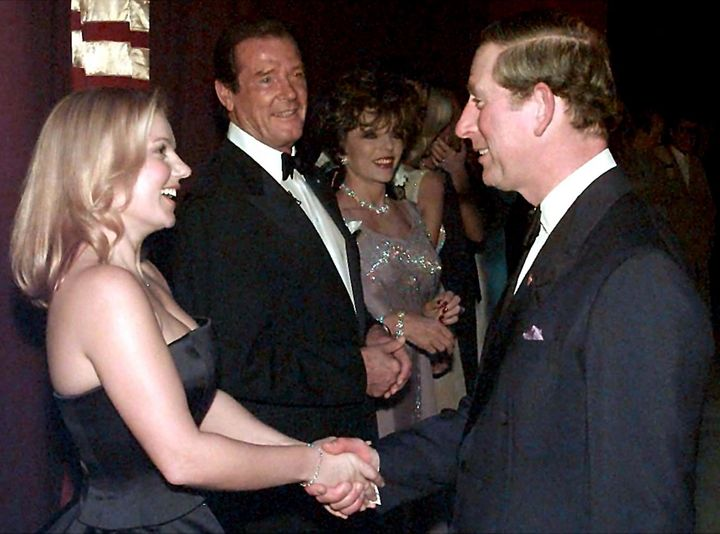"Prince Charles and Geri ""Ginger Spice"" Halliwell shake hands as Roger Moore and Joan Collins look on."