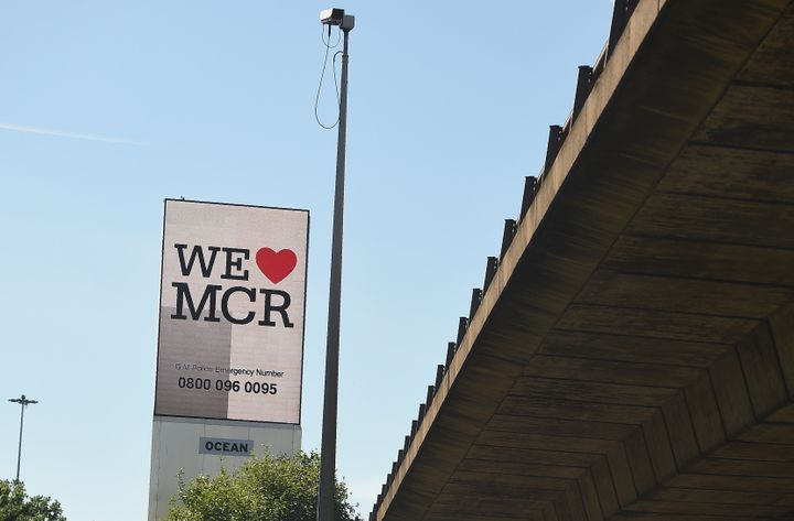"An electronic advertising board displays a ""We love MCR"" sign, along with a telephone number for Greater Manchester Police, n"