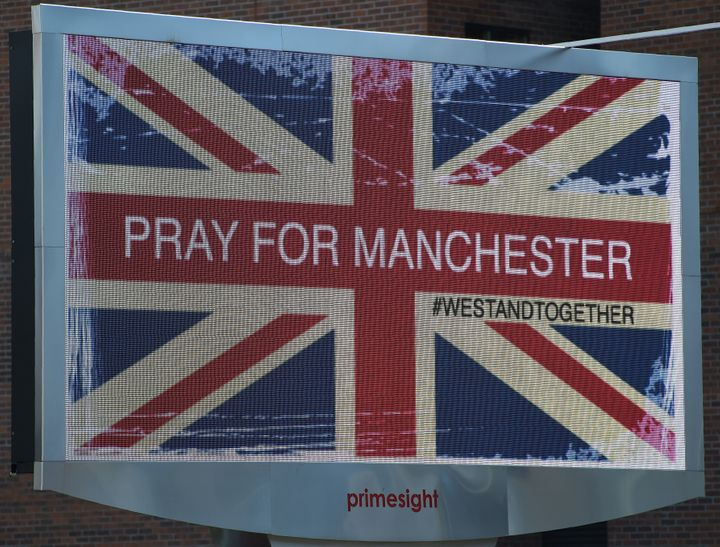 "An electronic advertising board displays a Union flag and the words ""Pray for Manchester,"" close to the Manchester Arena."