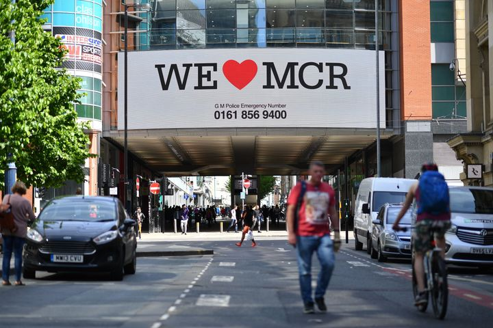 "A sign that reads ""We Love MCR"" is displayed in solidarity above a street in central Manchester, northwest England."