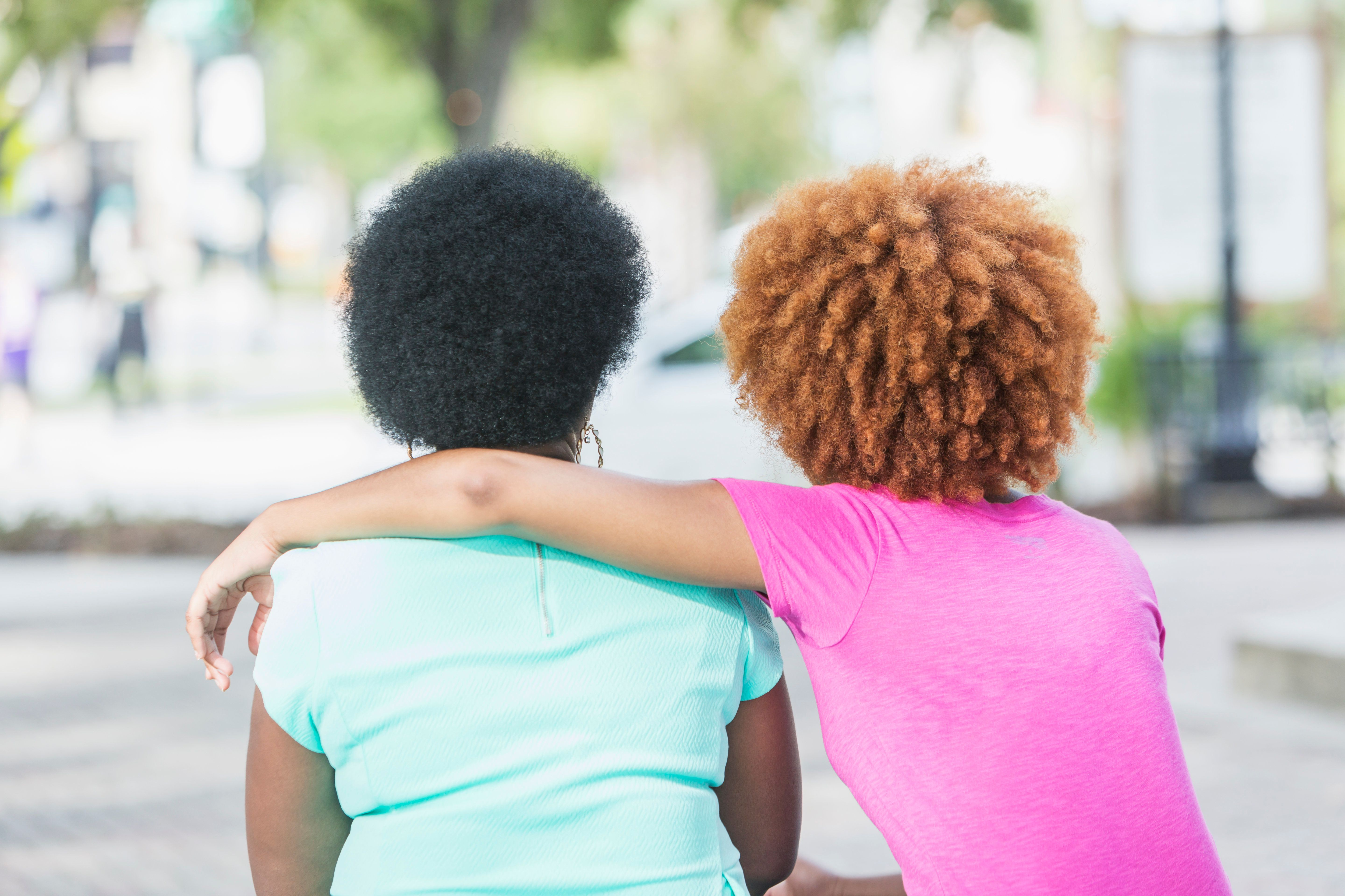 Rear view of an African American woman in her 50s sitting outdoors with her adult daughter, a young woman in her 20s with an afro and red dyed hair.
