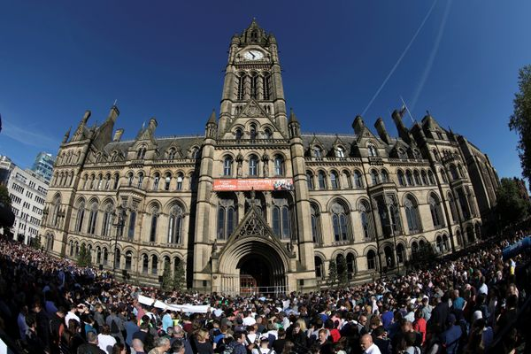 People attend a vigil for the victims in central Manchester.