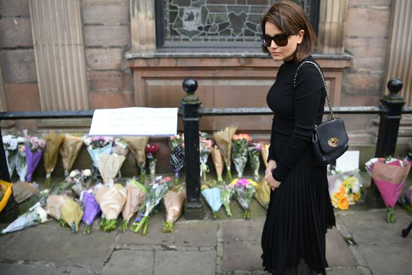 People leave flowers in St. Ann's Square in Manchester on Tuesday morning following a suicide attack at Manchester Arena.