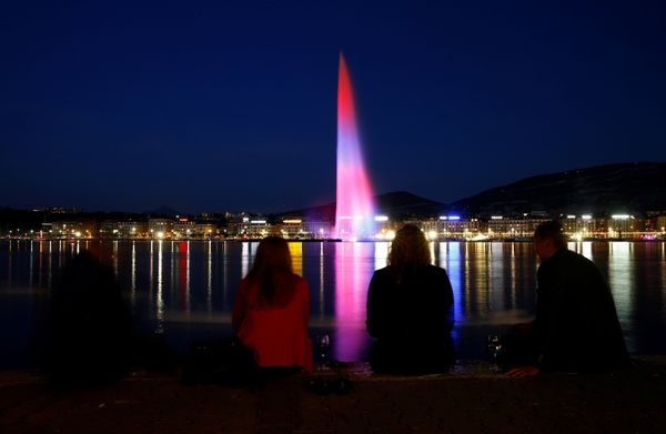 A water fountain (jet d'eau) in Geneva is lit with blue, red and white in remembrance of the victims of the Manches