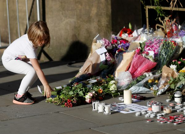 In central Manchester, a girl leaves flowers for the victims of the attack.