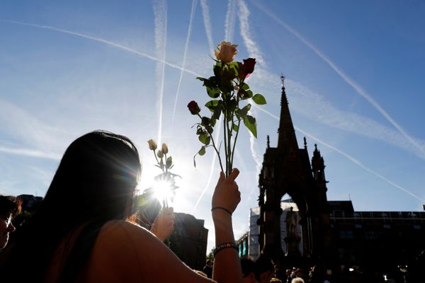 A woman holds flowers as she takes part in a vigil in central Manchester for the victims of the attack.