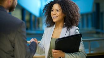 Young confident businesswoman shakes the hand of her potential new employer at her interview
