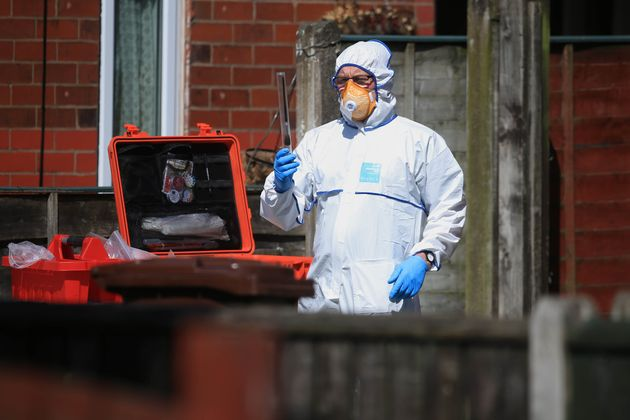 A police forensic investigator examines an address in Elsmore Road, linked
