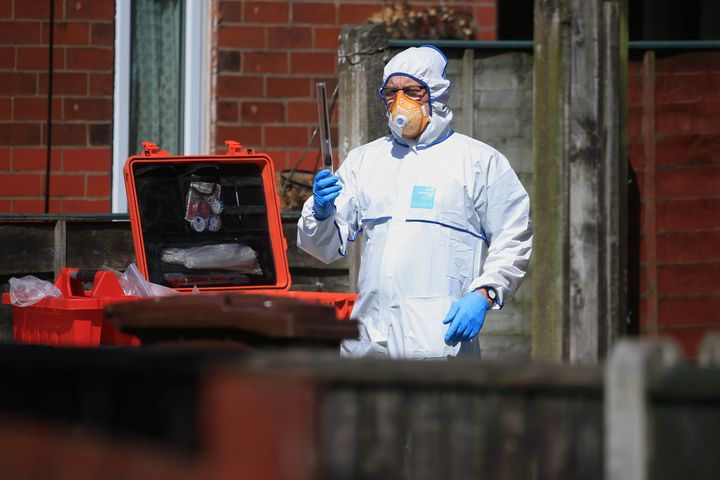 A police forensic investigator examines an address in Elsmore Road, linked toAdedi