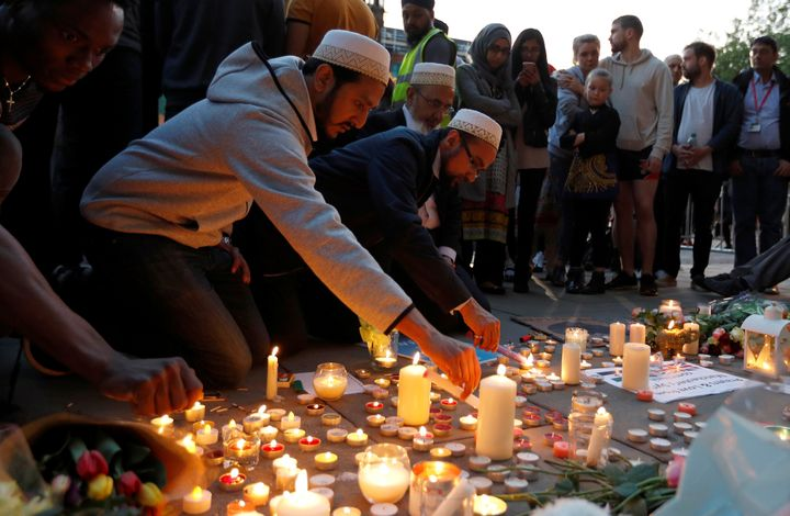 Men light candles following a vigil in central Manchester on Tuesday