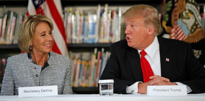 Secretary of Education Betsy DeVos and President Donald Trump participate in a round-table discussion during a visit to Saint