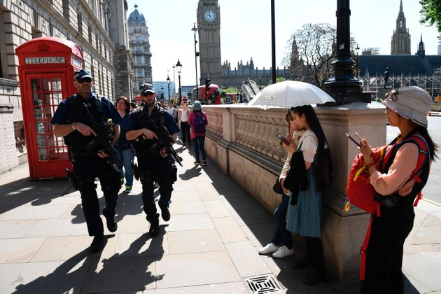 Tourists stand aside as two armed officers stride through Westminster on
