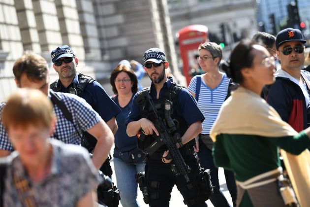 Armed police patrol a street near the Palace of Westminster housing the Houses of Parliament on