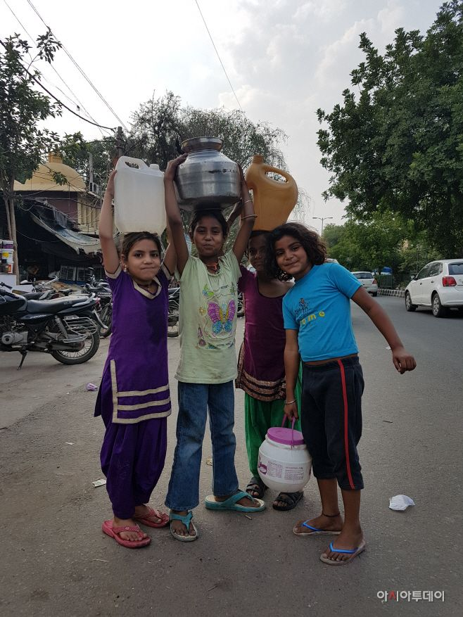 Girls are carrying big water buckets on their heads in Tamil Sangnam, New Delhi. However, some of them failed to fill their b