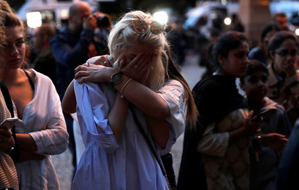 Women react after lighting candles for the victims of the attack.