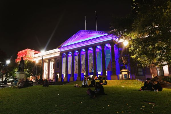 The colors of the Union Jack, the national flag of the United Kingdom, are projected onto the Victoria State Library as a tri