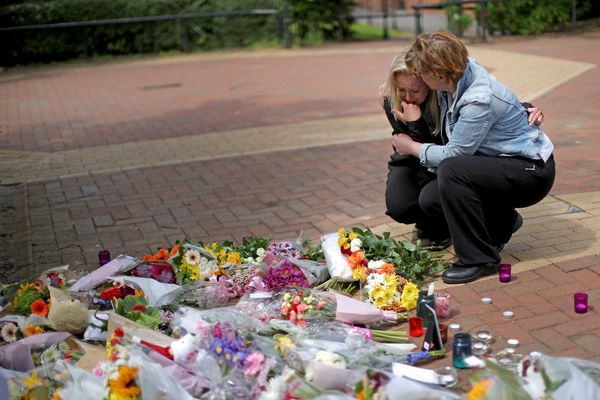 People lay flowers in center of the village of Tarleton to honor the victims of the Manchester attack.