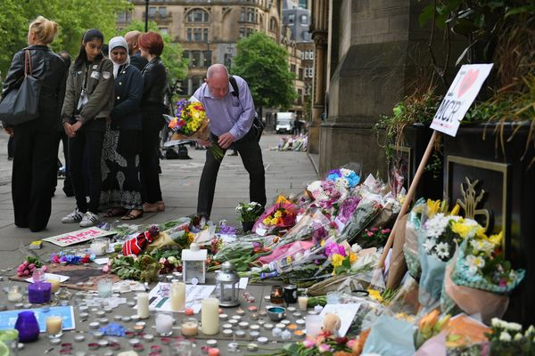 Members of the public pause to look at floral tributes and messages as the working day begins in Manchester.