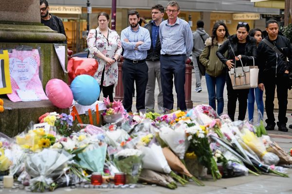 Members of the public pause to look at floral tributes and messages in St. Ann's Square in Manchester.