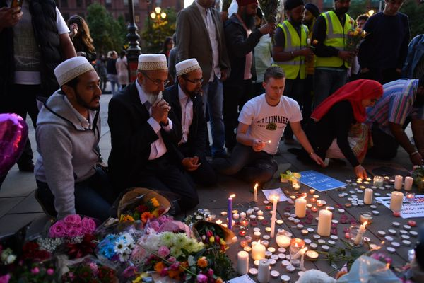People pray and light candles in Albert Square in Manchester.