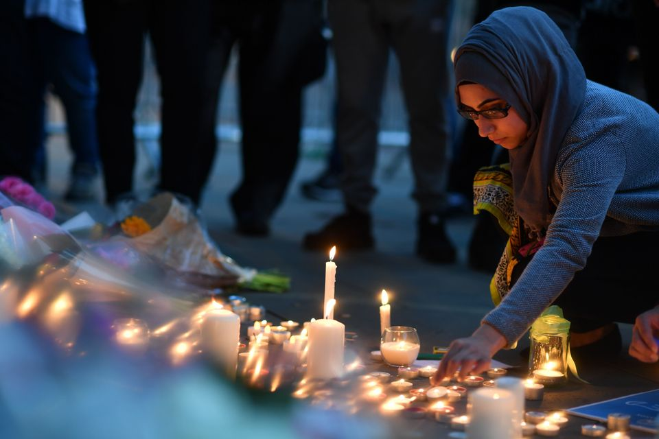 A woman lights candles at a vigil in Albert Square in Manchester, England.