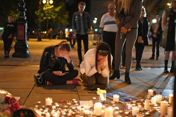 Members of the public attend a candlelit vigil, to honor the victims of Monday evening's terror attack, at Albert Square in M