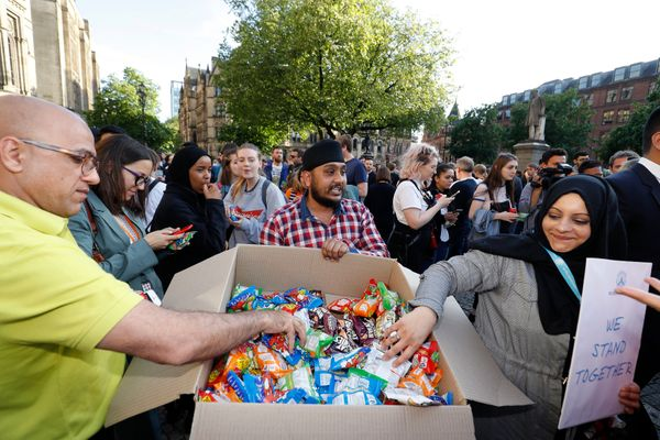 A man gives out food during a vigil in Albert Square, Manchester, after a 23-year-old man was arrested in connection with the