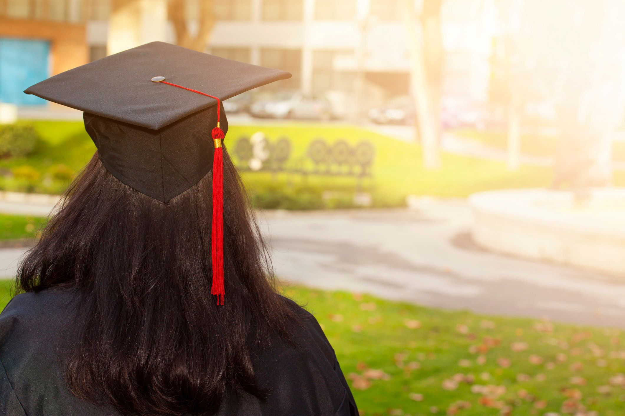 Rear view of a college graduate.  A young woman wearing a cap and gown.