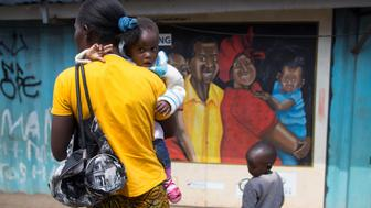 A woman walks past a murel during a visit by Netherlands Minister for Trade and Development Cooperation Lilianne Ploumen at a Family Health Options clinic in the Kibera slums in Nairobi, Kenya, May 16, 2017. picture taken May 16, 2017.REUTERS/Baz Ratner