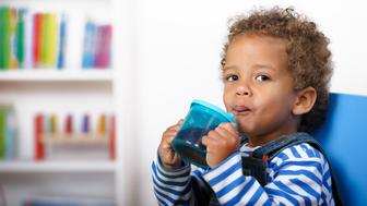 A happy biracial toddler enjoying a drink in a nursery setting.Converted from RAW. Nikon D3X.
