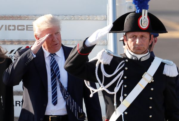 Trump salutes as he arrives at the Leonardo da Vinci-Fiumicino Airport in Rome, Italy.