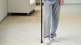Legs of senior man walking with cane