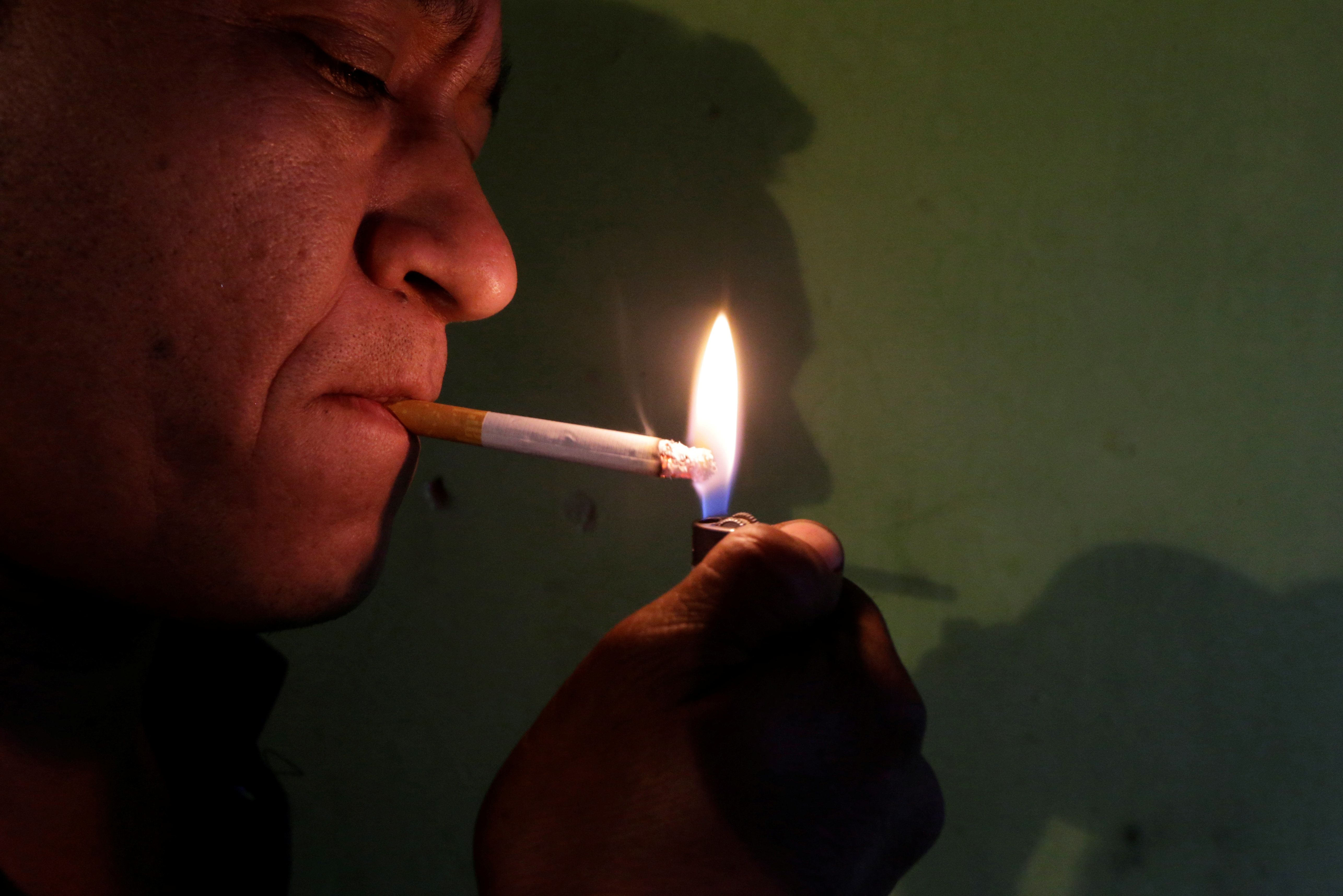 A man lights a cigarette in Asuncion, Paraguay May 11, 2017. Picture taken May 11, 2017. REUTERS/Jorge Adorno