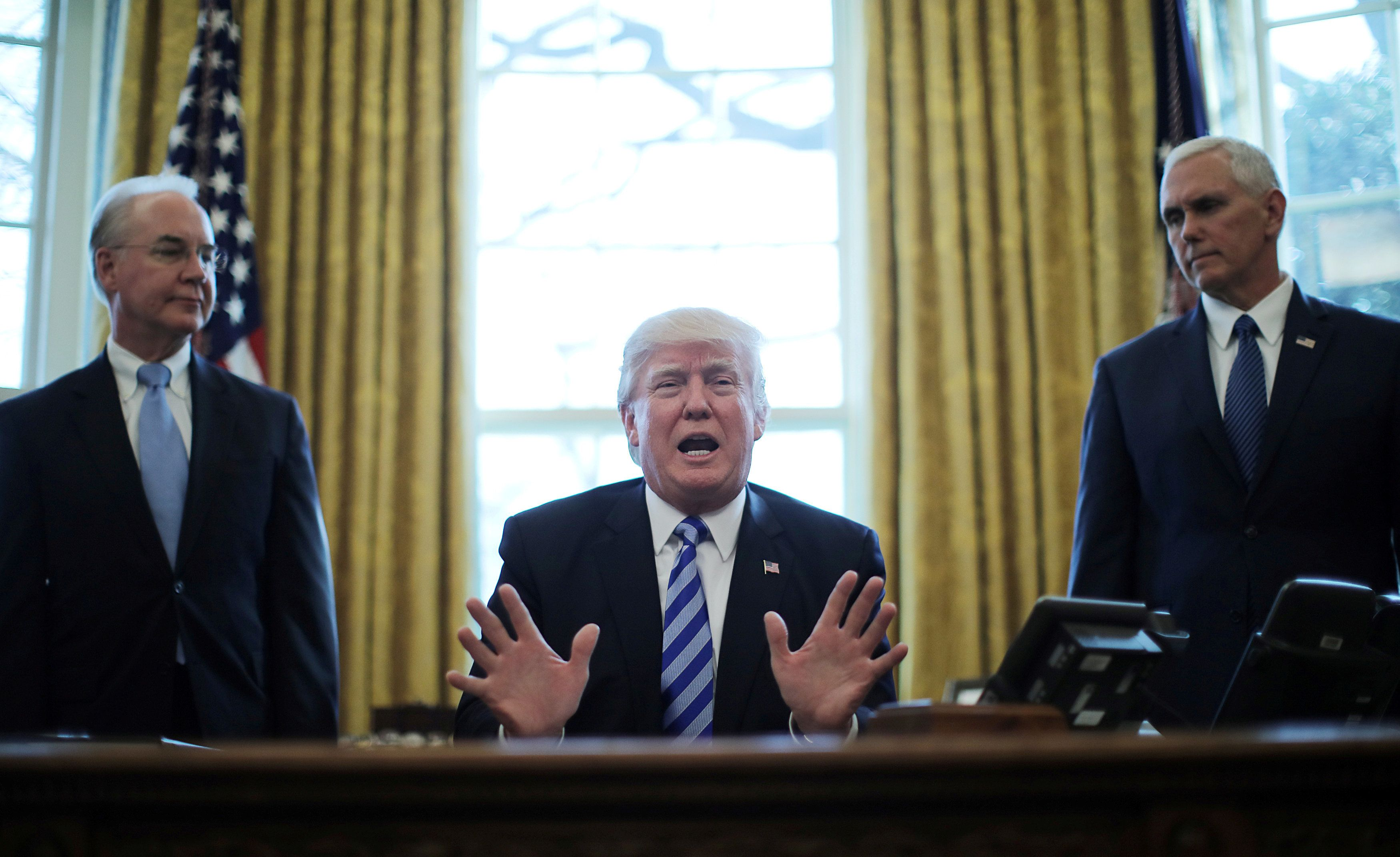 REFILE CORRECTING BYLINE - President Trump reacts to the AHCA health care bill being pulled by Congressional Republicans before a vote as he appears with Secretary of Health and Human Services Tom Price (L) and Vice President Mike Pence (R) in the Oval Office of the White House in Washington, U.S., March 24, 2017. REUTERS/Carlos Barria