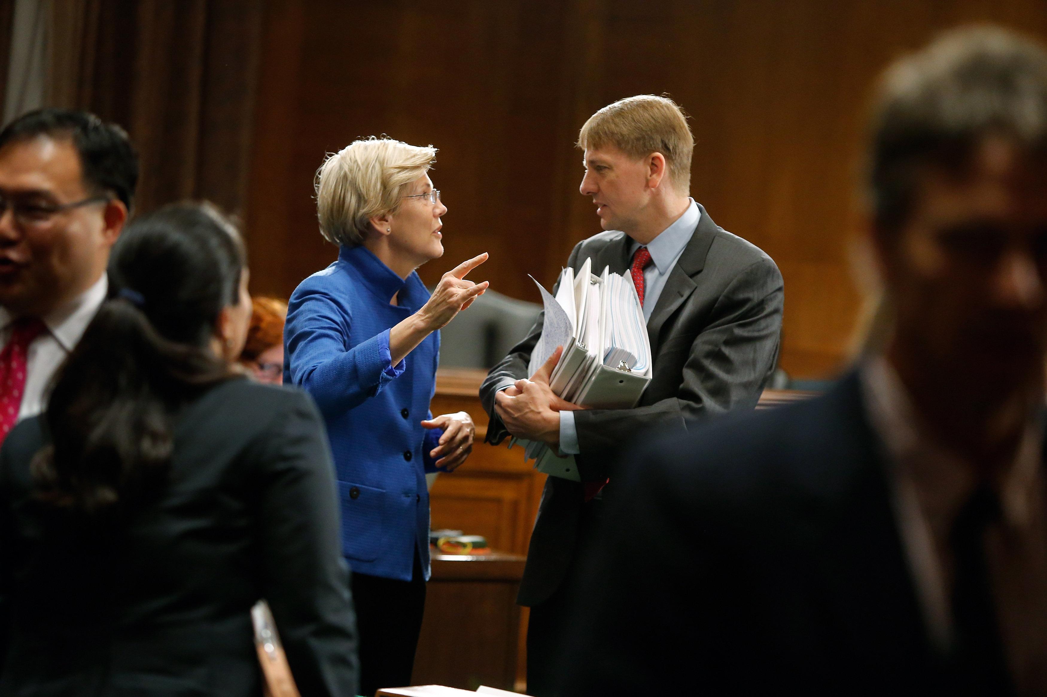 Sen. Elizabeth Warren (D-Mass.) talks with Consumer Financial Protection Bureau Director Richard Cordray after he testified o