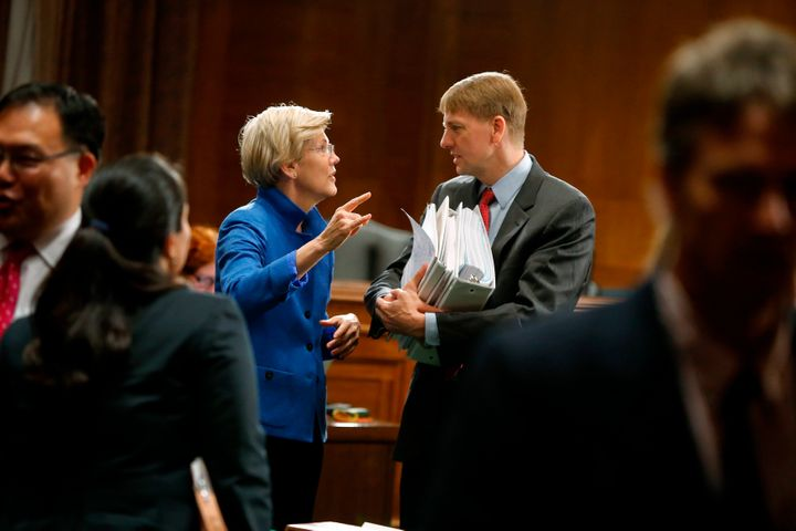 Sen. Elizabeth Warren (D-Mass.) talks with Consumer Financial Protection Bureau Director Richard Cordray after he testified o