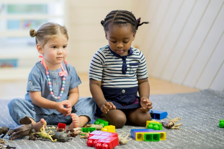 A group of toddlers are playing with toys together in preschool. FatCamera via Getty Images