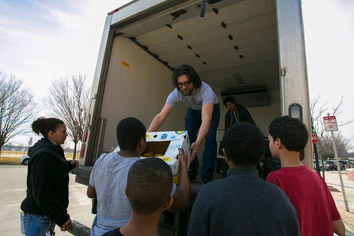 Lovin' Spoonfuls driver Vinny Vassallo distributes food to a beneficiary in South Boston