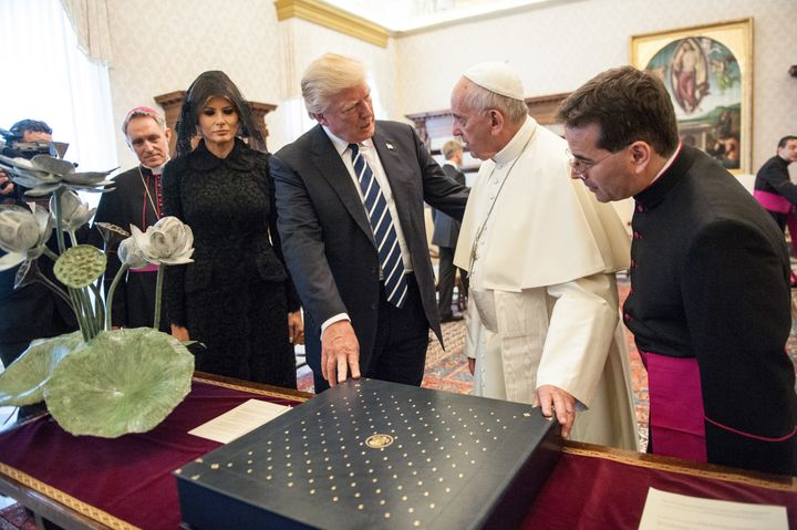 Pope Francis exchanges gifts with United States President Donald Trump and First Lady Melania Trump during an audience at the