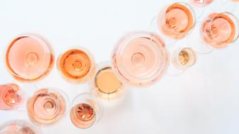 Many glasses of rose wine at wine tasting. Concept of rose wine and variety. White background. Top view, flat lay design. Natural light.