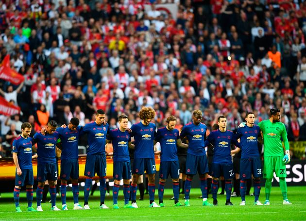 Manchester United's players observe a minute's silence for the victims of the bomb attack in Manchester...