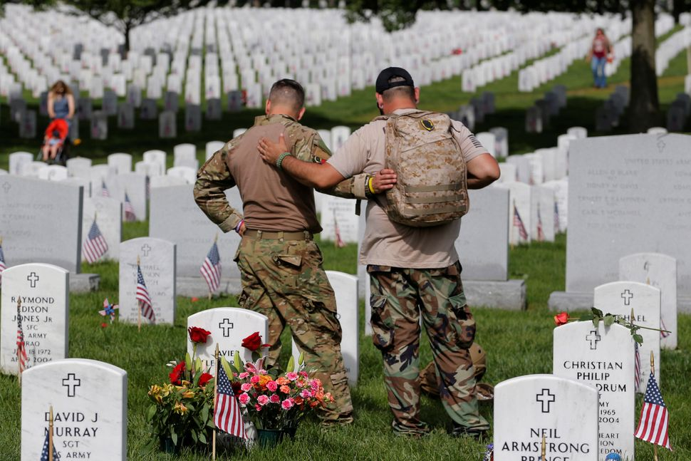 U.S. Army soldiers Rick Kolberg, left,  and Jesus Gallegos embrace as they visit the graves of Raymond Jones and Peter E