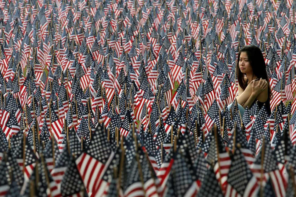 A woman sits at the edge of the field of United States flags displayed by the Massachusetts Military Heroes Fund on the Bosto