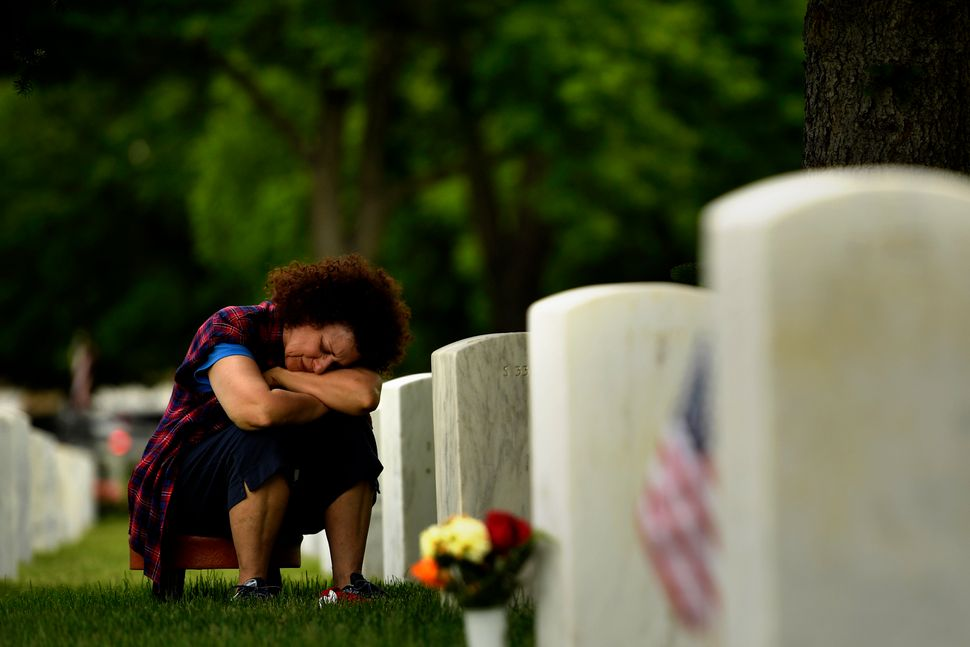 Andi Schorr grieves at the grave of her husband Sergeant First Class George Joseph Schorr. Schorr served two tours of duty in