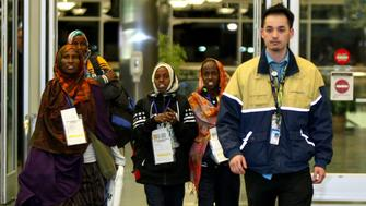 Safiya Hassan, Dahaba Matan, Farduwsa Matan, and Nima Matan, refugees from Somalia, are escorted by a United Airlines representative before being met by their U.S.-based family members on arrival at the airport in Boise, Idaho, U.S. March 10, 2017.  REUTERS/Brian Losness